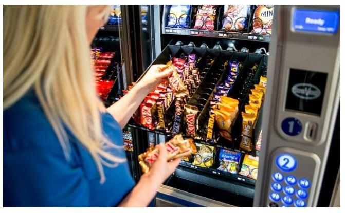 Mulher abastecendo chocolates em vending machine