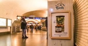 Homem olhando para a vending machine da empresa Take Fresh em estação de metrô. Ao fundo pessoas transitam no corredor